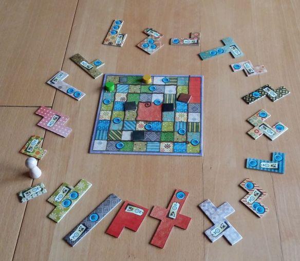 Die Zeitspirale liegt in der Mitte, die Flicken darum herum. Zur Auswahl stehen dem aktiven Spieler immer nur die nächsten drei Flicken vor der großen Spielfigur.