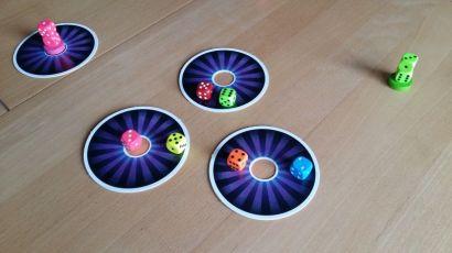 Die drei Lochscheiben liegen in der Mitte, die Spieler postieren sich rundherum. Der rosa Würfel links gibt sofort einen Siegpunkt, Der höhere Würfel gewinnt die Scheibe.