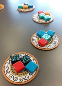 Die Steine liegen in der Tischmitte immer in Vierer-Paketen. Man kann einzelne Steine nehmen, der Rest wandert in die Tischmitte und bildet dort eine neue Auslage
