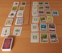 Die zentrale Auslage des Kartenspiels für vier Spieler. Gewürfelt wir mit aufgedruckten Würfeln.